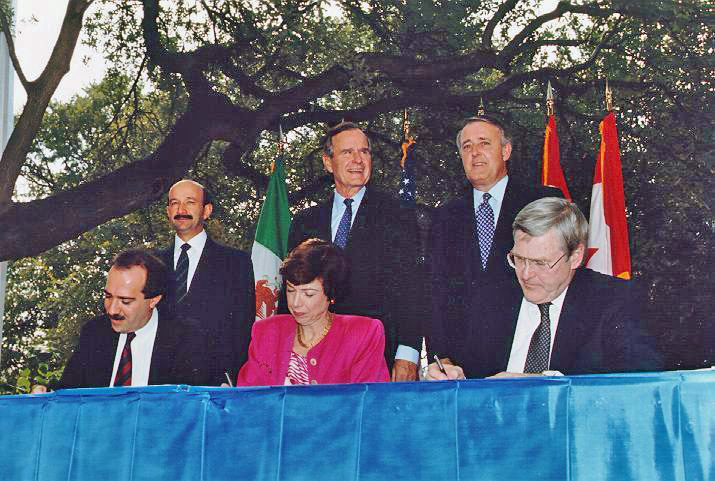 Back row, left to right: Mexican President Carlos Salinas de Gortari, U.S. President George H. W. Bush, and Canadian Prime Minister Brian Mulroney, at the signing of the North American Free Trade Agreement in October 1992. In front are Mexican Secretary of Commerce and Industrial Development Jaime Serra Puche, United States Trade Representative Carla Hills, and Canadian Minister of International Trade Michael Wilson. NAFTA Initialing Ceremony, October 1992 From left to right (standing) Mexican President Carlos Salinas de Gortari, US President George H. W. Bush, Canadian Prime Minister Brian Mulroney. (Seated) Mexican Secretary of Commerce and Industrial Development Jaime Serra Puche, United States Trade Representative Carla Hills, Canadian Minister of International Trade Michael Wilson